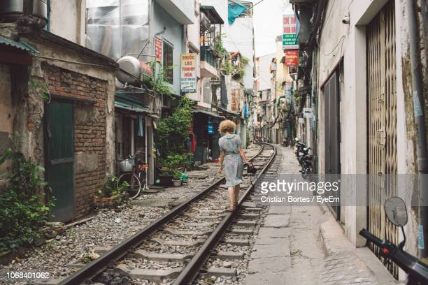 Woman Walking On Railroad Track Amidst Buildings In City