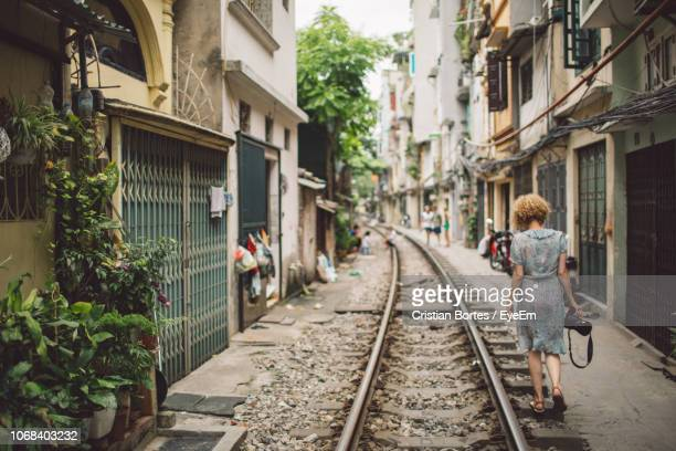 Woman Walking On Railroad Track In City