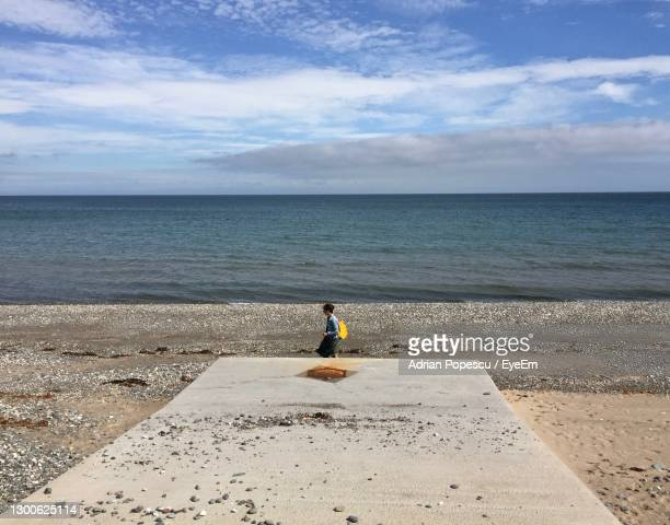 woman walking on ramsey beach in the isle of man - side view stock pictures, royalty-free photos & images