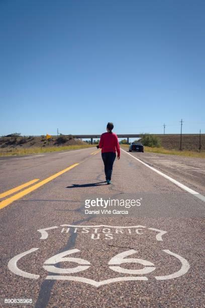 Woman walking on remote desert road