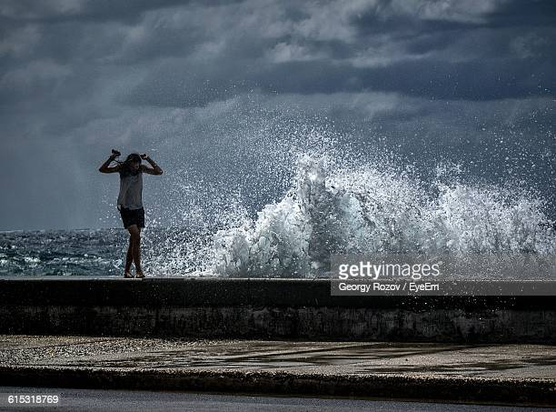 woman walking on retaining wall during high tide against storm clouds - retaining wall stock pictures, royalty-free photos & images