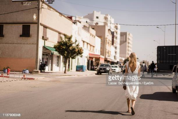 woman walking on road in city - agadir stock pictures, royalty-free photos & images