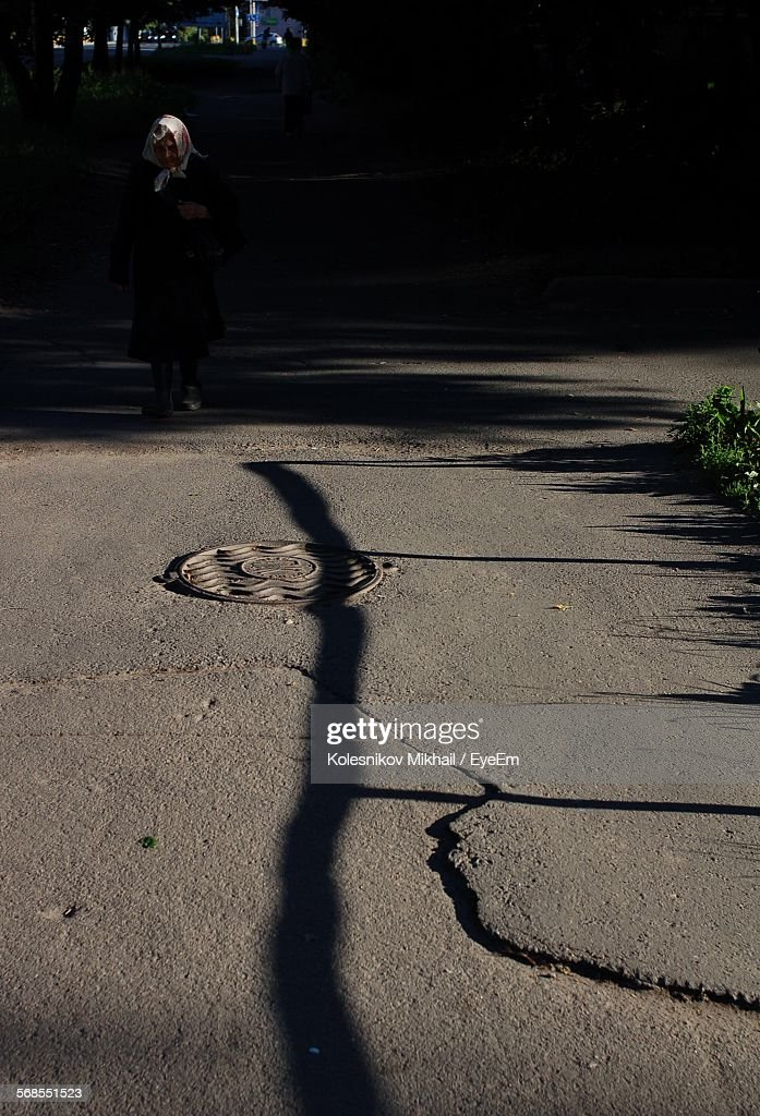 Woman Walking On Road In Front Of Manhole : Stock Photo