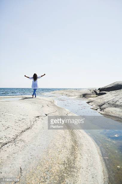 woman walking on rock with arms up - one mature woman only stock pictures, royalty-free photos & images