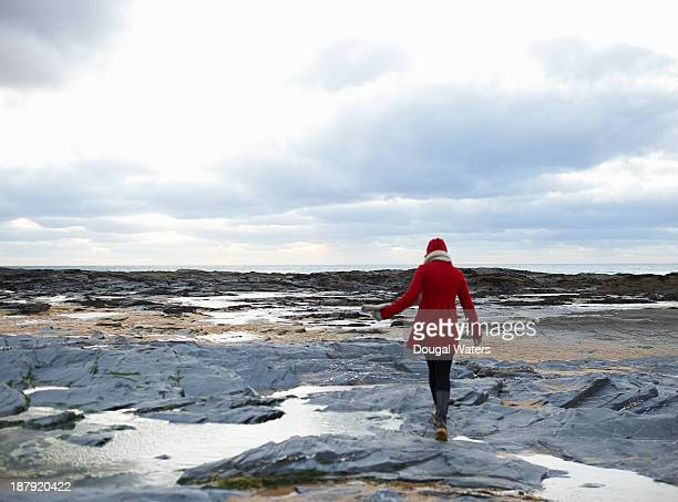 woman walking on rocky coastline. - red coat stock pictures, royalty-free photos & images