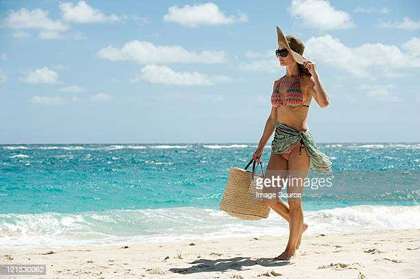 woman walking on sandy beach, mustique, grenadine islands - woman carrying tote bag stock photos and pictures