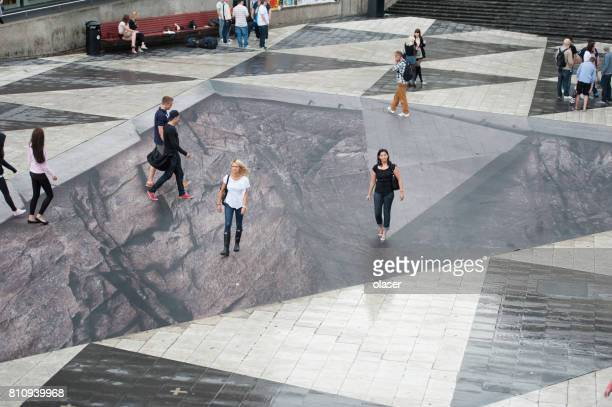 woman walking on sergels torg square illusion - illusion stock pictures, royalty-free photos & images