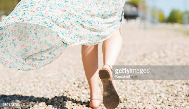 Woman walking on shingle beach