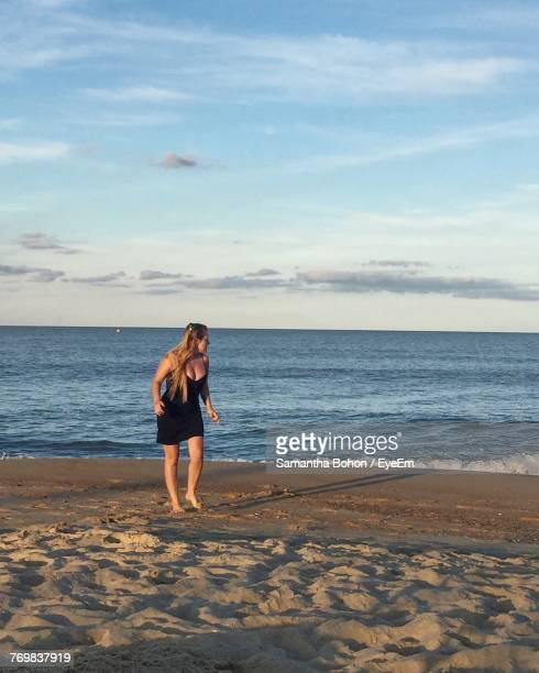 woman walking on shore at beach against sky - kitty hawk beach stock pictures, royalty-free photos & images