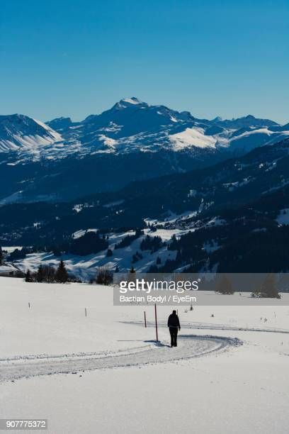 Woman Walking On Snow Covered Road Against Sky