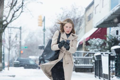 Woman walking on snowy street - gettyimageskorea