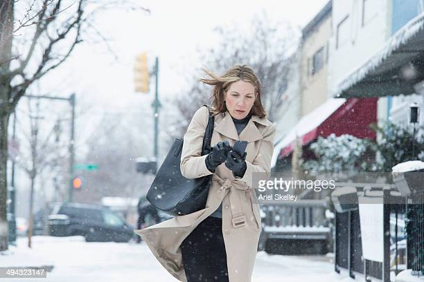 woman walking on snowy street - kälte stock-fotos und bilder