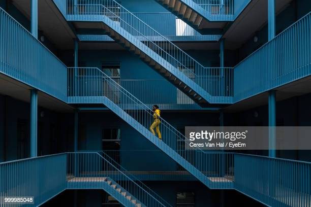 woman walking on staircase of building - degraus e escadas - fotografias e filmes do acervo