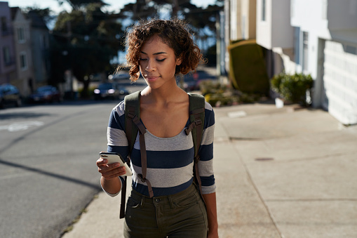 Woman walking on steep road and looking at smartphone - gettyimageskorea