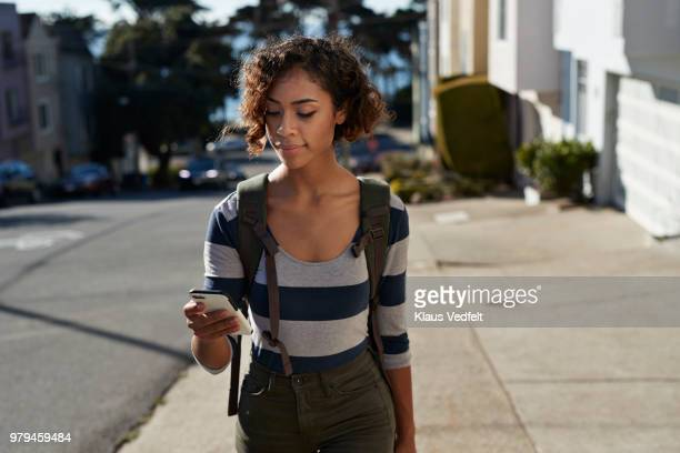 woman walking on steep road and looking at smartphone - short hair stock pictures, royalty-free photos & images