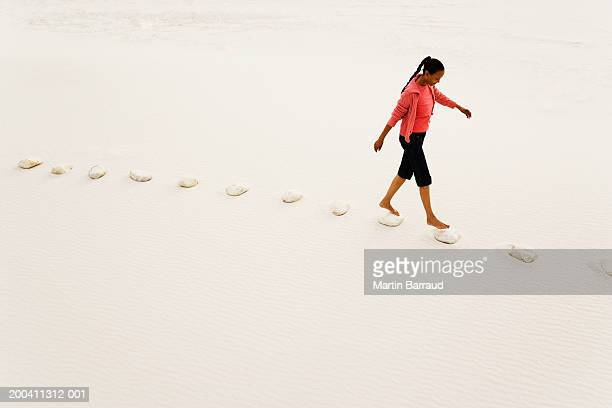 Woman walking on stepping stones on white sandy beach, elevated view