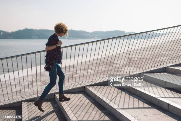woman walking on steps in city - bortes stock photos and pictures