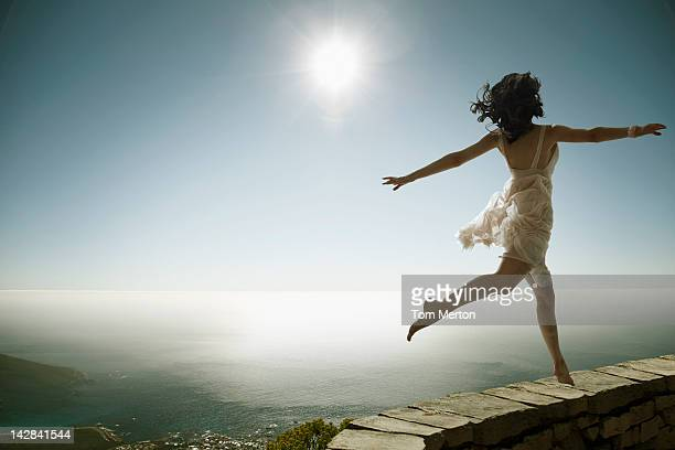 Woman walking on stone wall on cliff