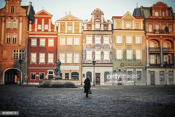 Woman Walking On Street Against Buildings