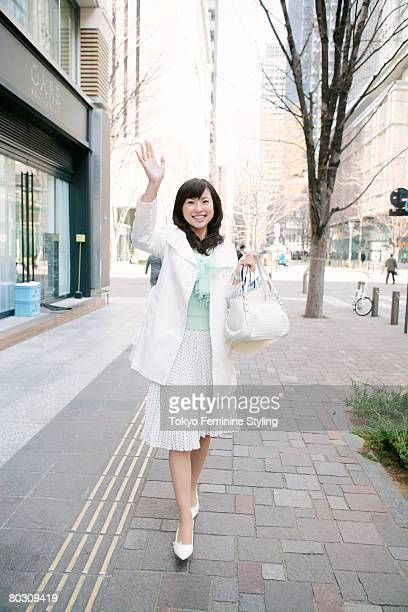 Woman walking on street and waving