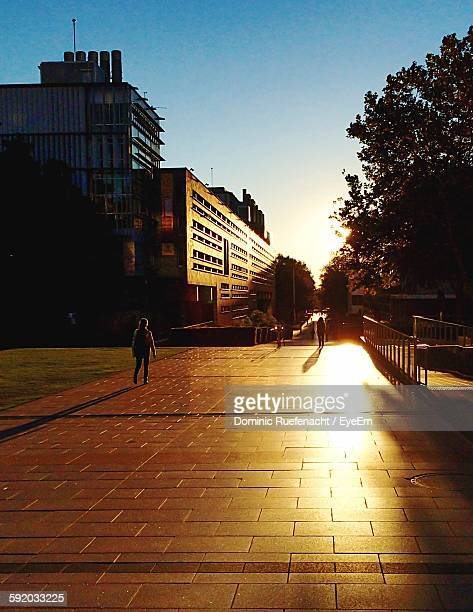 Woman Walking On Street By Building Against Sky During Sunset