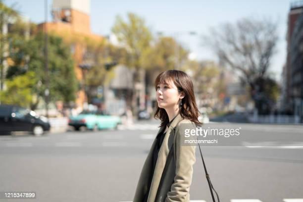 ダウンタウンの通りを歩いている女性 - アベニュー ストックフォトと画像