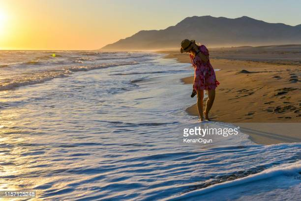 woman walking on the beach at sunset. - kas stock pictures, royalty-free photos & images