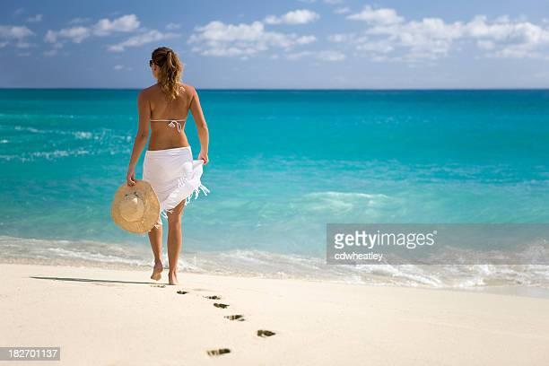 Mujer caminando en la playa en el paraíso caribeño