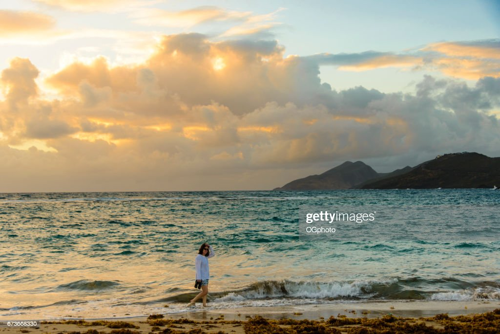 Woman walking on the beach in the early morning. : Stock Photo