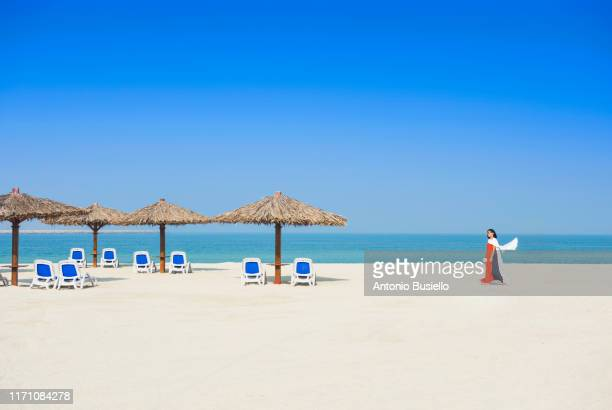 woman walking on the beach - dubai strand stock-fotos und bilder