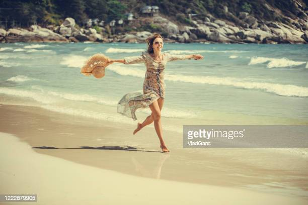 woman walking on the beach - vintage fashion stock pictures, royalty-free photos & images