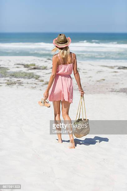 woman walking on the beach - woman carrying tote bag stock photos and pictures