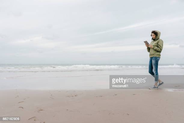 Woman walking on the beach with tablet