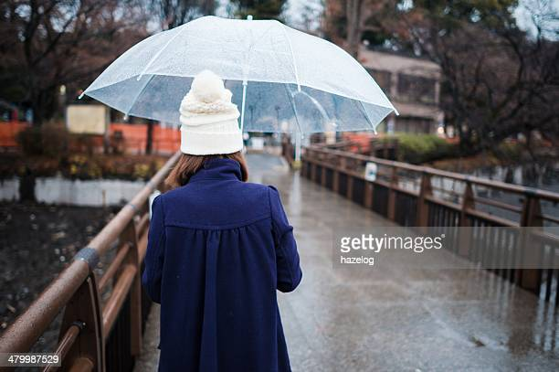 Woman walking on the bridge on a rainy day