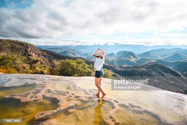 woman walking on the limestone rock formations at hierve el agua, oaxaca, mexico - travel stock pictures, royalty-free photos & images