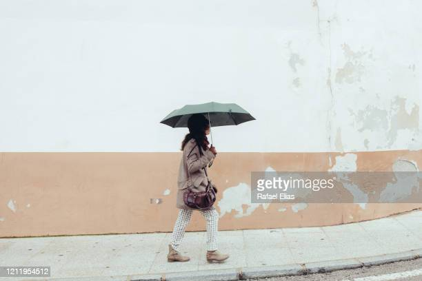 woman walking on the sidewalk with an umbrella - caceres stock pictures, royalty-free photos & images
