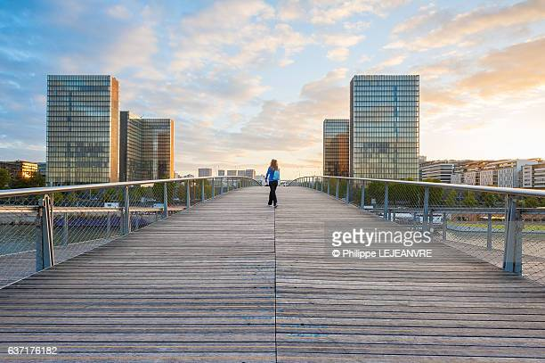 woman walking on the simone de beauvoir footbridge at sunset - footbridge stock photos and pictures