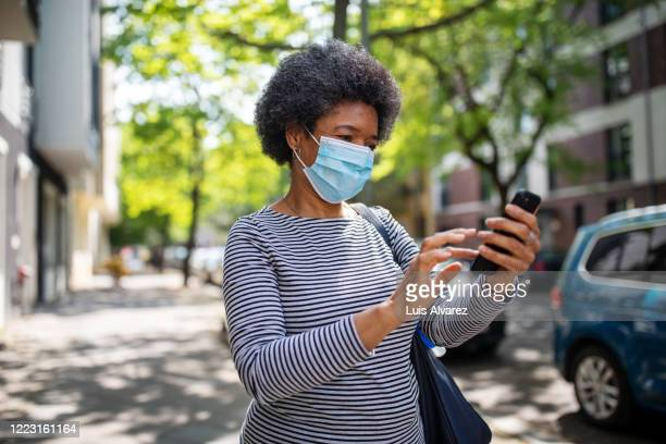 woman walking on the street during corona virus outbreak using phone - essential services stock pictures, royalty-free photos & images