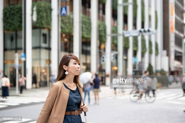 woman walking on the street of shopping area - ginza stock pictures, royalty-free photos & images