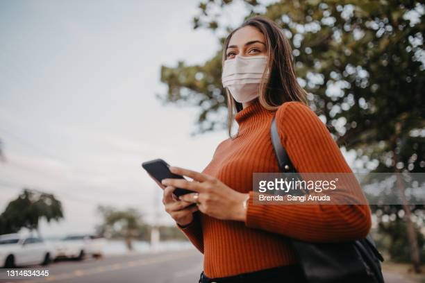 woman walking on the street with protective mask - world sports championship stock pictures, royalty-free photos & images