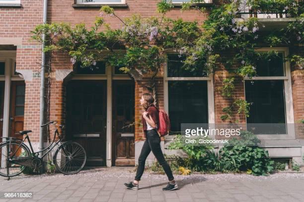vrouw lopen op de straten van amsterdam - nederlands stockfoto's en -beelden
