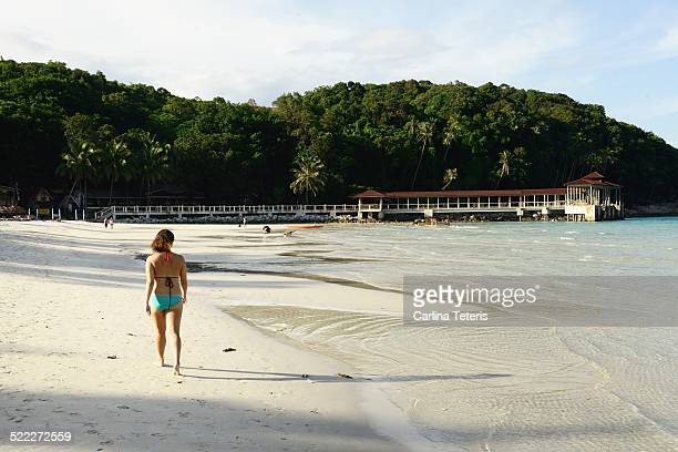 woman walking on tropical beach - terengganu stock pictures, royalty-free photos & images