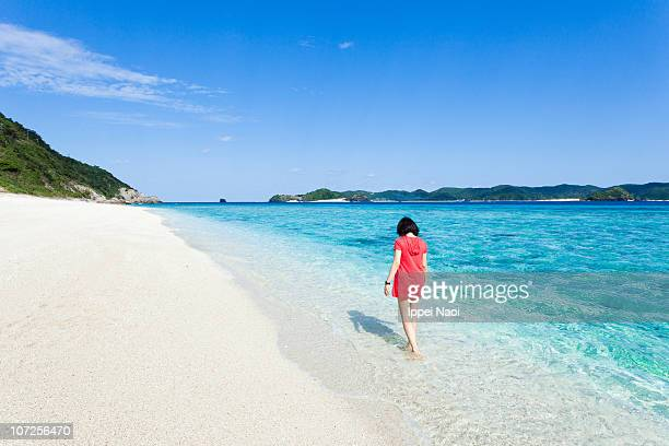 Woman walking on tropical beach with clear water