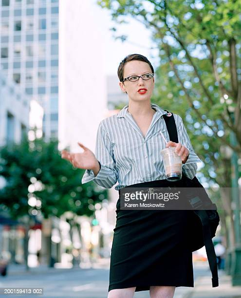 woman walking on urban sidewalk, carrying coffee drink - coffee drink stock pictures, royalty-free photos & images