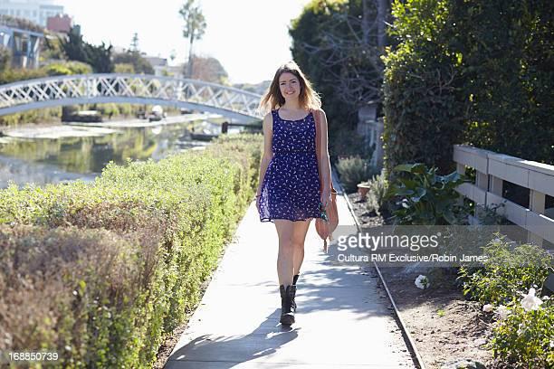Woman walking on urban waterfront