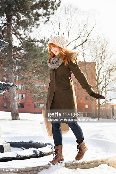 Woman walking on wall in snow