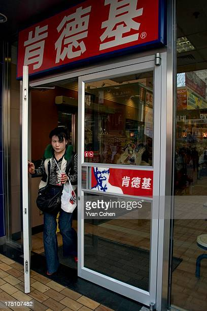 A woman walking out of a Kentucky Fried Chicken outlet in Kunming