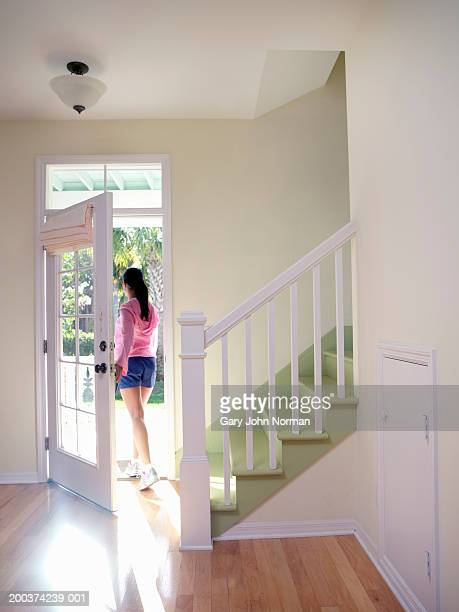 Woman walking out of house, rear view