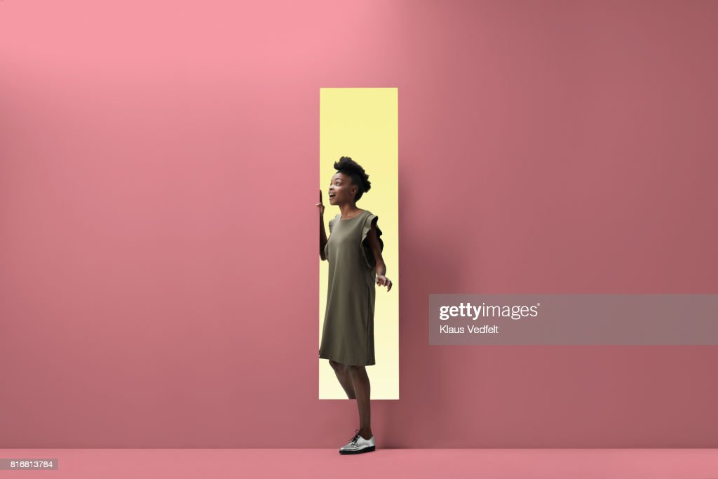 Woman walking out of rectangular opening of coloured wall : ストックフォト