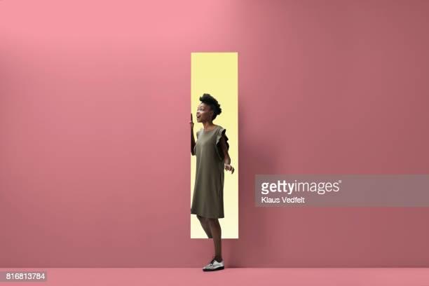 woman walking out of rectangular opening of coloured wall - verwachting stockfoto's en -beelden